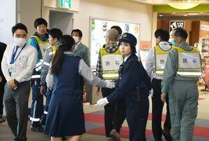 テロ対処訓練で利用者を安全な場所場まで避難誘導する警官や空港関係者=佐賀市の佐賀空港