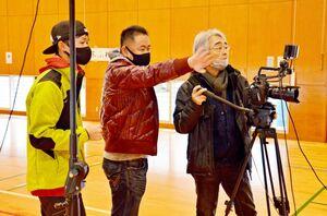 撮影に臨む江口監督(中央)=唐津市鎮西町の波戸岬少年自然