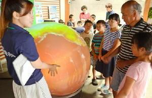 デジタル地球儀で温暖化の様子などを見る来場者たち=鹿島市の生涯学習センター「エイブル」