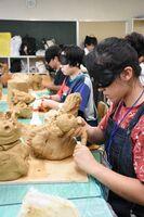 美術・工芸の研修講座。目隠ししながら、感性に任せて粘土で鳥を制作する生徒=佐賀市の佐賀西高校