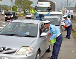 早めのライト点灯を促すチラシなどをドライバーに手渡す交通指導員たち=上峰町役場横の県道