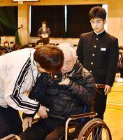 贈った車いすに乗る老人ホームの男性利用者を見守る石井啓貴さん(右)=佐賀市の城西中学校