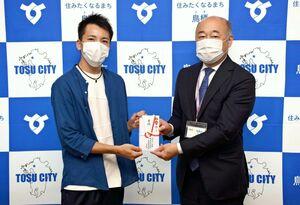 橋本康志市長(右)に寄付を手渡す学生会長の吉高仁さん=鳥栖市役所