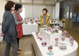 桜の花やバラなど、さまざまな花を使ったボトルフラワー約150点が並ぶ=佐賀市のアバンセ