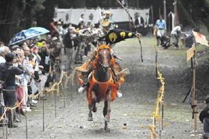 小雨の中、疾走する馬上から見事に的を射抜く射手=みやき町の白石神社