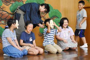 子どもたちが能面をつけると少し大きく、滑稽な姿に笑いが起きていた=佐賀市松原の井内能舞台
