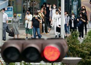 マスク姿で信号待ちをする人たち=10日午後、東京・新宿