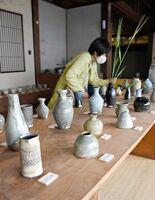 山野草が引き立つ、優しい色味の花器が並ぶ川口武亮さんの作品展=唐津市北波多の草伝社