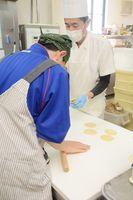 パン製造の体験でパンの生地を伸ばす高校生と、ボルガのオーナーシェフ坂井啓太さん(右)=佐賀市木原のボルガ