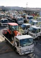 初荷式では、トラクターやコンバインなどを載せたトラックが続々と出発した=佐賀市久保田町のJA農業機械総合センター