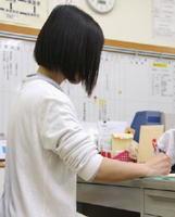 午後8時を過ぎても、学校の職員室でプリントの添削をする女性教諭=中国地方