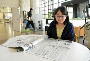 昼休みに新聞を開き、地域のニュースなどを読む学生=佐賀市本庄町の佐賀大学附属図書館