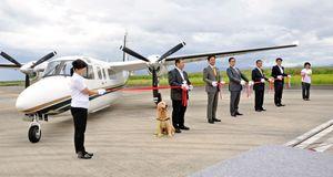 発足した「空飛ぶ医師団」の専用航空機の前でテープカットをする関係者=佐賀市川副町の佐賀空港